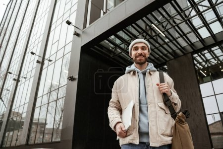 low angle view of happy freelancer in beanie hat holding laptop
