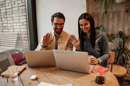 happy freelancers waving hands while using laptops on table