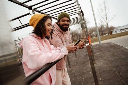 Photo pour Joyeuse sportive afro-américaine bavardant sur smartphone près d'un ami, au premier plan flou - image libre de droit