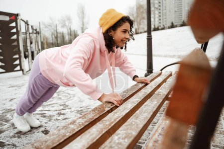 smiling african american sportswoman doing push ups near bench outdoors, blurred foreground