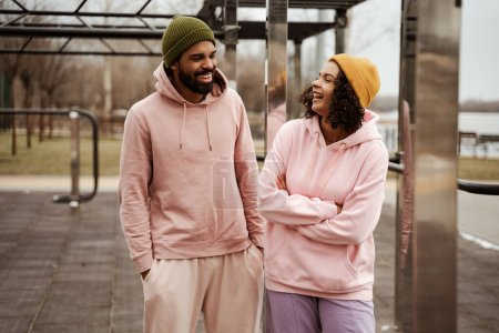 cheerful african american couple in sportswear looking at each other while talking outdoors