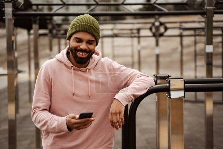 Photo for Joyful african american man in sportswear chatting on cellphone on sports ground - Royalty Free Image