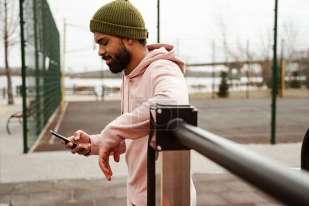 Photo for Side view of bearded african american sportsman messaging on mobile phone, blurred foreground - Royalty Free Image