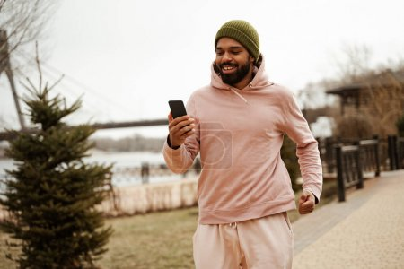 cheerful african american jogger holding mobile phone while running outdoors