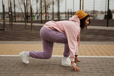 Photo pour Vue latérale du joggeur afro-américain debout en position de départ bas à l'extérieur - image libre de droit