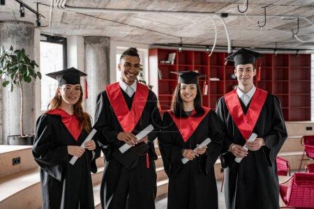 Photo pour Heureux interracial étudiants en robes de graduation et casquettes détenant un diplôme, senior 2021 - image libre de droit