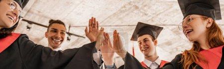 Photo pour Heureux étudiants interraciaux en robes et casquettes détenant un diplôme et donnant cinq, classe de graduation 2021, bannière - image libre de droit