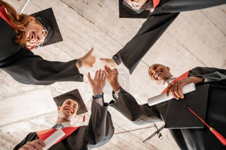 Photo for Bottom view of happy interracial students in graduation gowns and caps holding diploma and giving high five - Royalty Free Image
