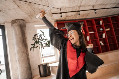 excited student in glasses, graduation cap and gown holding diploma