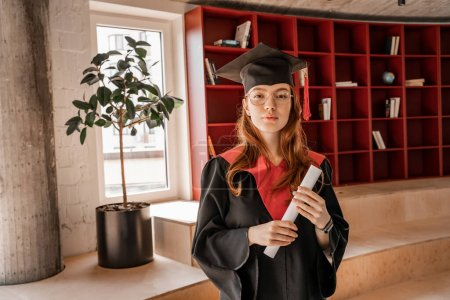 Photo for Redhead student in graduation cap and gown holding diploma - Royalty Free Image