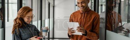 Photo pour Heureux étudiant afro-américain en utilisant tablette numérique près de camarade de classe avec smartphone, bannière - image libre de droit