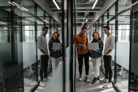 Photo pour Pleine longueur de l'étudiant joyeux en utilisant un ordinateur portable près de camarades de classe interracial - image libre de droit