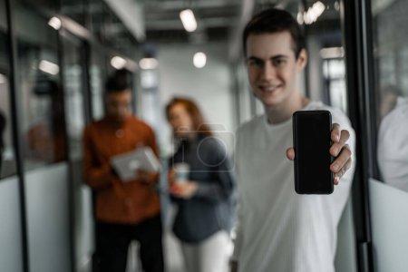 Photo pour Heureux étudiant tenant smartphone avec écran vide près de camarades de classe interracial sur fond flou - image libre de droit