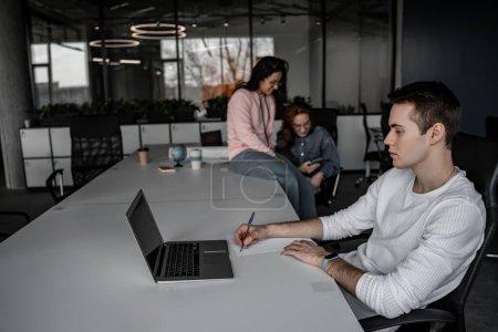 jeune étudiant écrit sur papier tout en regardant ordinateur portable près des femmes sur fond flou