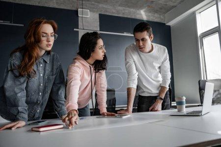 Photo pour Jeunes étudiants regardant du papier avec un projet sur le bureau - image libre de droit
