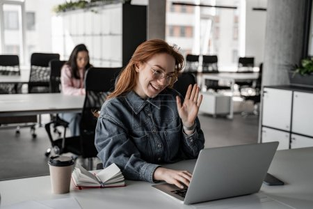cheerful redhead student waving hand while having video chat on laptop
