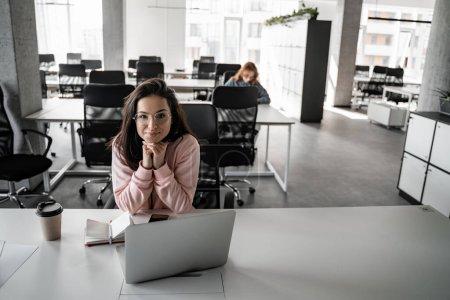 Photo pour Femme brune heureuse dans des lunettes regardant la caméra près de gadgets sur la table - image libre de droit