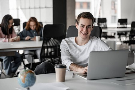 happy student using laptop and paper cup and globe on table