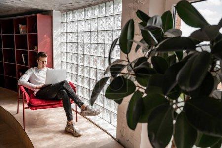 Photo pour Jeune étudiant utilisant un ordinateur portable assis dans un fauteuil, senior 2021 - image libre de droit
