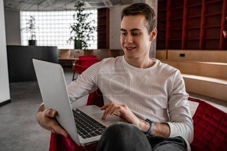 joyeux jeune étudiant utilisant un ordinateur portable tout en étant assis dans le fauteuil, senior 2021