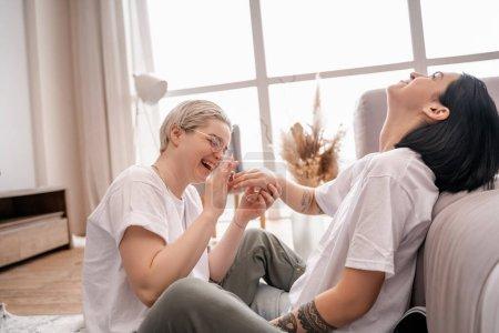 Photo pour Femme heureuse dans des lunettes portant bague sur doigt de petite amie - image libre de droit