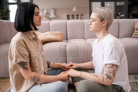 Photo for Side view of lesbian couple sitting and holding hands while meditating in living room - Royalty Free Image