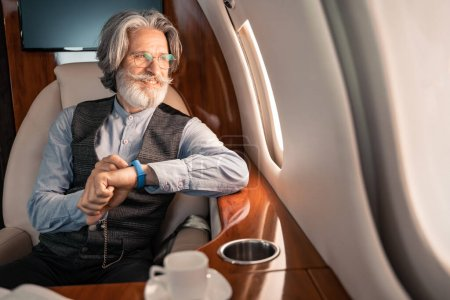 Photo for Smiling businessman with smartwatch looking at window near coffee in plane - Royalty Free Image