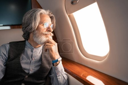Photo for Mature man in eyeglasses and smartwatch looking at window in plane - Royalty Free Image
