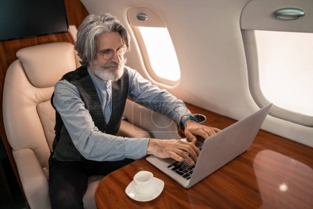 Photo for Mature businessman using laptop near coffee in airplane - Royalty Free Image