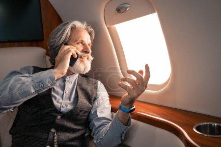 Photo pour Homme d'affaires mature souriant parlant sur smartphone et regardant la fenêtre de l'avion - image libre de droit