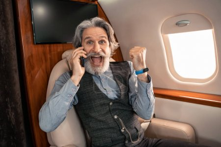 Excited businessman talking on smartphone and showing yes gesture in plane