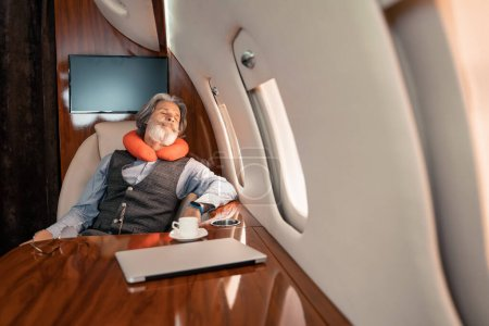 Mature businessman in neck pillow sleeping near laptop and coffee in plane