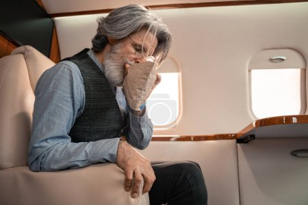 Photo for Mature man breathing in air sickness bag in private jet - Royalty Free Image