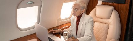 Businesswoman using laptop near glass of champagne in jet, banner