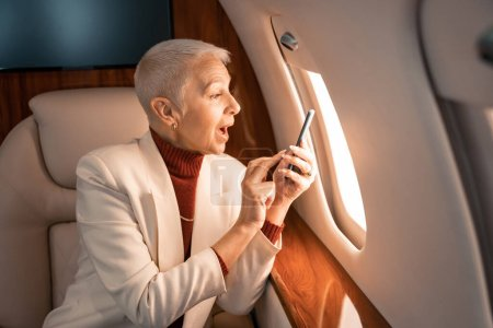 Photo for Amazed businesswoman with smartphone looking at window in private plane - Royalty Free Image