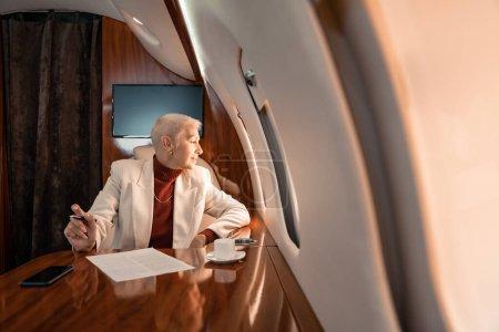 Photo pour Femme d'affaires mature souriante regardant la fenêtre de l'avion près du café et du papier - image libre de droit