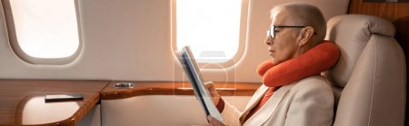 Photo for Side view of mature businesswoman in neck pillow reading magazine in private jet, banner - Royalty Free Image
