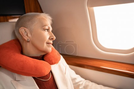 Femme d'affaires mature dans l'oreiller du cou regardant la fenêtre de l'avion