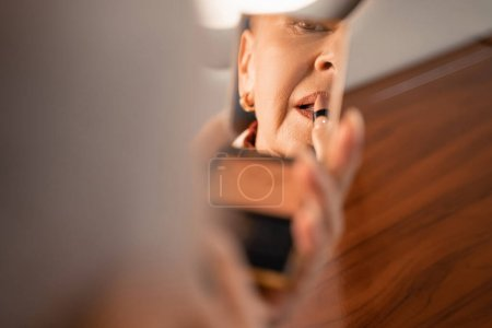 Mature woman applying lipstick and looking at mirror in plane