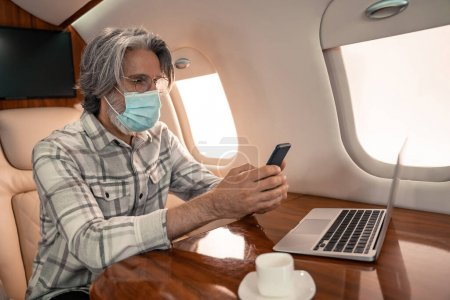 Photo for Businessman in medical mask using smartphone near laptop and coffee in airplane - Royalty Free Image