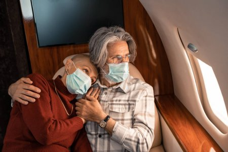 Photo for Man in medical mask hugging wife in private jet - Royalty Free Image