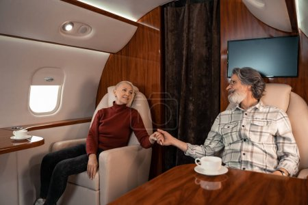 Photo for Smiling mature couple holding hands near cups of coffee in private plane - Royalty Free Image