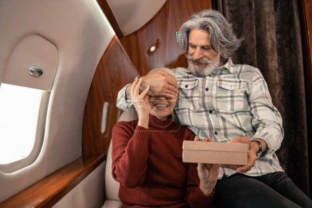 Photo for Smiling man holding gift box and covering eyes of wife in private plane - Royalty Free Image