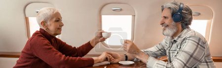 Photo for Side view of smiling woman holding cup near husband in headphones in plane, banner - Royalty Free Image