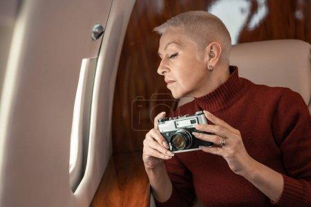 Photo for Mature woman holding retro camera near window on plane - Royalty Free Image