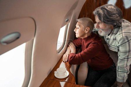 Mature man hugging smiling wife near window of plane