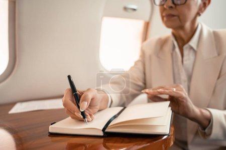 Photo pour Vue recadrée d'une femme d'affaires floue écrivant sur un carnet en jet privé - image libre de droit