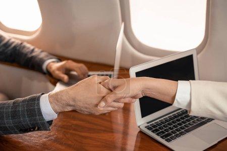 Photo pour Vue recadrée de gens d'affaires serrant la main près des ordinateurs portables dans l'avion - image libre de droit