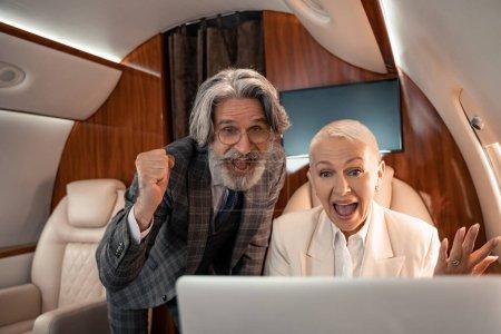 Photo pour Des hommes d'affaires excités regardant un ordinateur portable flou dans un avion privé - image libre de droit