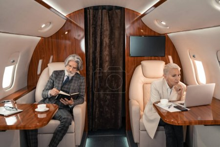 Businesswoman looking at laptop near businessman with notebook in airplane